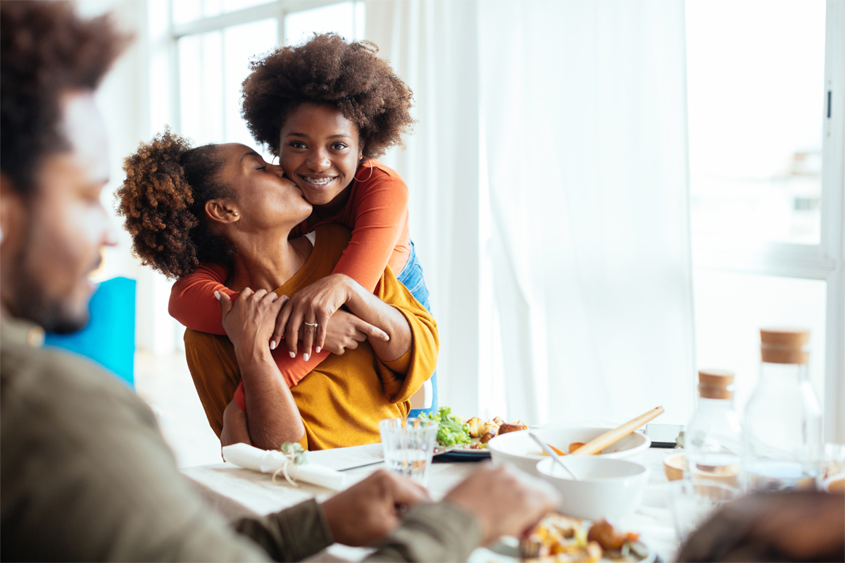 Mom and daughter embracing at dinner table